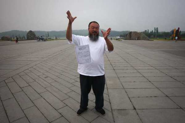 Ai Weiwei drops a copy of a government document informing him of the expiration of his bail term in a park in Beijing on Thursday.