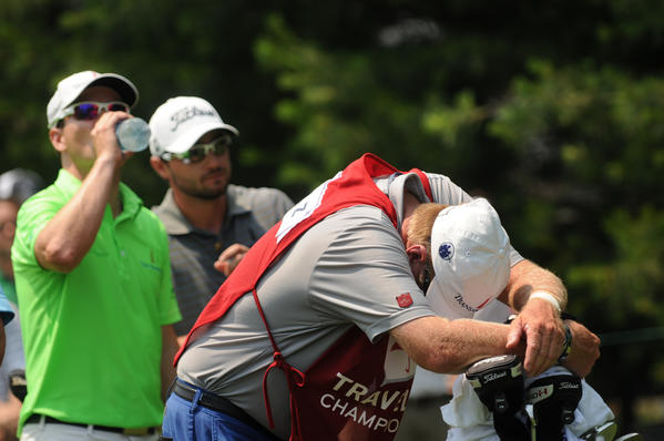 Damon Green, caddie for Zach Johnson, momentarily rests his head on the bag while waiting at the 8th tee in the second round of the Travelers Championship at the TPC at River Highlands Friday. Johnson (left) takes a drink of water as he waits with Kyle Stanley (center).