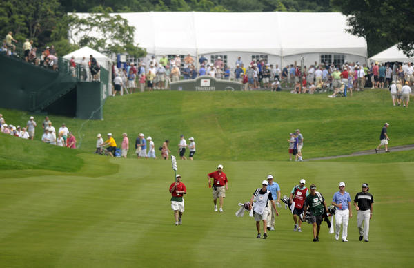 Webb Simpson, (second from lower right) winner of the U.S. Open last week, and Bubba Watson, (lower right) winner of the Masters, walk down the 1st fairway in the second round of the Travelers Championship at the TPC at River Highlands Friday.  A large gallery followed the two popular players around the course.