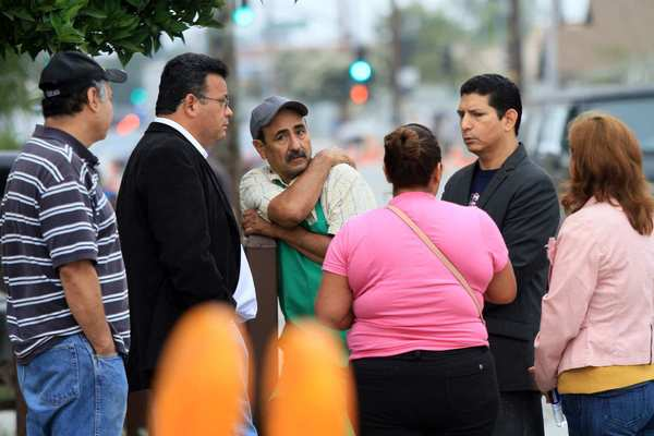 Family members and friends of Cudahy City Councilman Osvaldo Conde stand outside the shopping plaza that was being raided by the FBI.