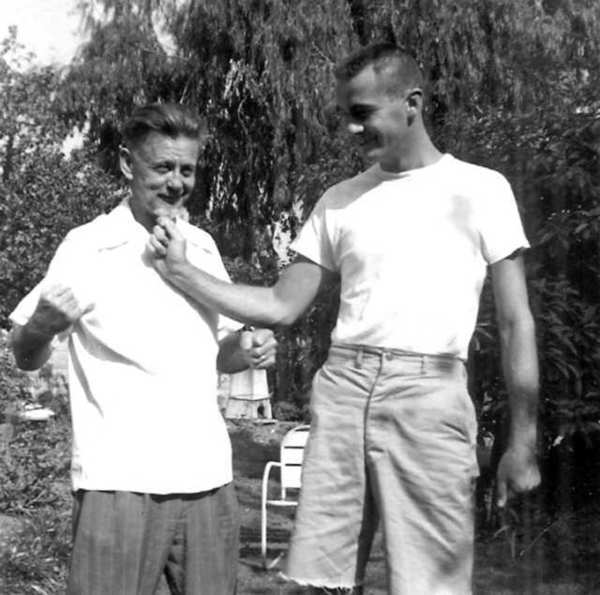Legory O'Loughlin, laughs as his son, Tom, checks out the beard he is growing in anticipation of the citys celebration of fifty years of city hood in 1956.