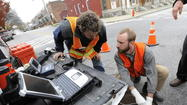 City workers check storm drain for sewage leak