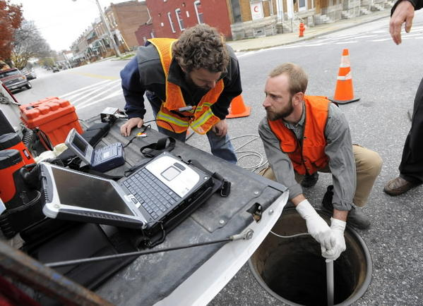 Michael Schlenoff and Matt Cherigo with the Department of Public Works, use a camera to see down into the storm drain to check for sewage leaks at corner of E. Chase St and N. Milton Ave. in East Baltimore.