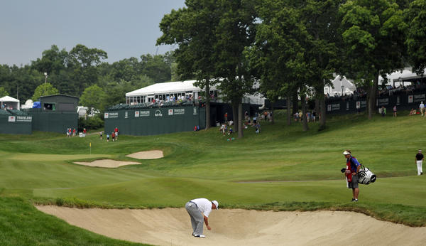 Chris DiMarco marks his tee shot in the fairway bunker on the 18th hole during the second round of the 2012 Travelers Championship golf tournament at the TPC River Highlands in Cromwell Thursday. Play was suspended for the second time at 3:19 pm as players wait for a decission on when play will resume.