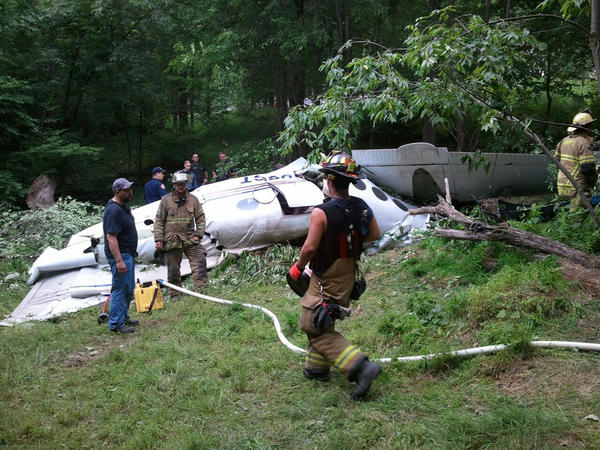 In this photo provided by Mike Nichols of Aphelion Aviation, emergency personnel work the scene of a small plane crash in Coopers Rock State Forest, 7.5 miles east of Morgantown, W.Va. on Friday, June 22. 2012. Monongalia County Sheriff Al Kisner confirmed one person was killed when the Hawker Beechcraft BE90 struck a radio tower and crashed.