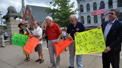 Kimberly Bennett, Frank Fantauzzo, Silverset Gjurich, of Johnstown, Joe Atal of Ebensburg and Mark Pasquerilla of Johnstown hold up signs supporting the Route 219 project during a press event held by U.S. Rep. Mark Critz on the Somerset County Courthouse steps Friday.