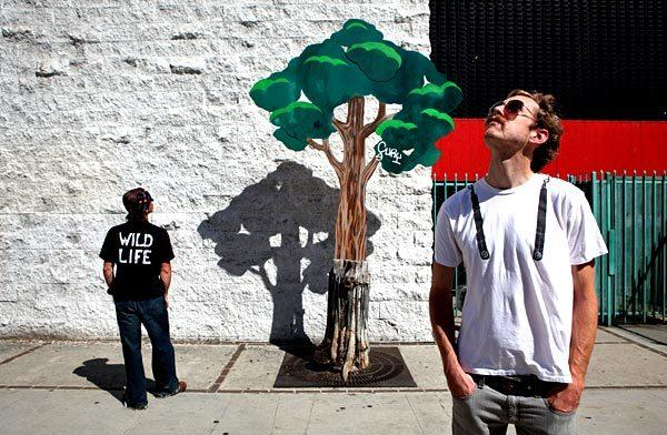 Artists Calder Greenwood, right, and his partner, Wild Life, stand next to one of their installations on Spring Street. The pair collaborate on papier-mache street art that they put up in downtown Los Angeles.
