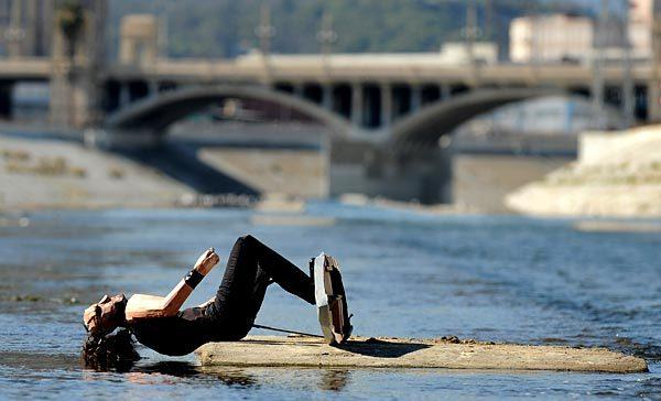 A papier-mache surfer falls into the L.A. River near the 6th Street Bridge. Its creators, Calder Greenwood and a man known only as Wild Life, posed the surfer and similar papier-mache sculptures in areas of downtown Los Angeles that are often walked by but unnoticed, such as vacant lots.