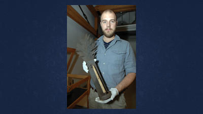 Curator Jacob Miller holds a tinned short iron candle sconce that once hung in Holy Trinity Lutheran Church in Berlin. It was made by Nelson Geary, who lived from 1820 until 1910.