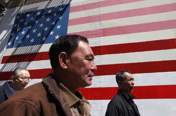 Pedestrians walk by an American flag mural in San Francisco, Calif. According to a study released last week by the Pew Research Center, Asian Americans are now the largest group of new immigrants to the United States bringing the population of Asian Americans to a record 18.2 million.