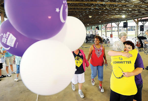 Three year cancer survivor Debbie Slick, right, in purple, hugs her sister and caregiver Ruth Smith after the caregiver lap Friday at the Ag Center.