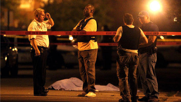 Chicago police stand near the scene of a homicide in the Englewood neighborhood on June 22, 2012.