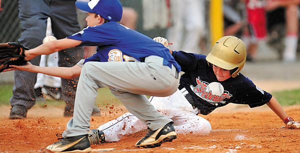 Federal's Braden Kolb slides safley into home plate as the ball gets away from Clear Spring's Mike Myers in the second inning Friday.