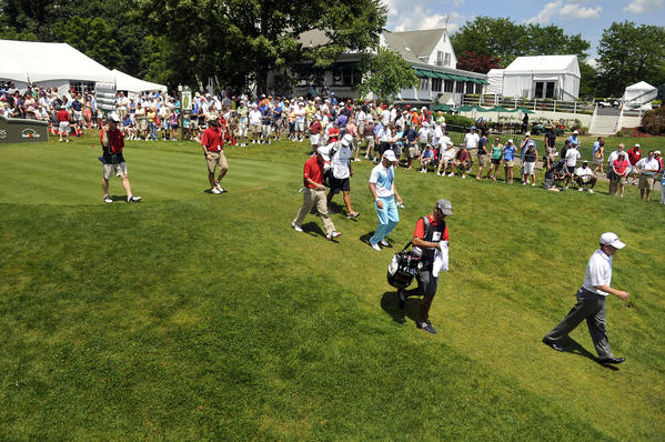 The group of Jeff Maggert, Brian Harman and Graham DeLaet head down the 1st tee during the third round of the 2012 Travelers Championship golf tournament at the TPC River Highlands in Cromwell Saturday. Play was late getting strated due to inclement weather Friday which had to be finished this morning.