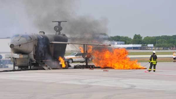 Flames roar from a mock aircraft at the start of the emergency response exercise at Midway Saturday.