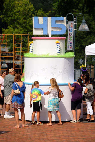 People gather around a giant birthday cake to sign it during Columbia's 45th birthday celebration.
