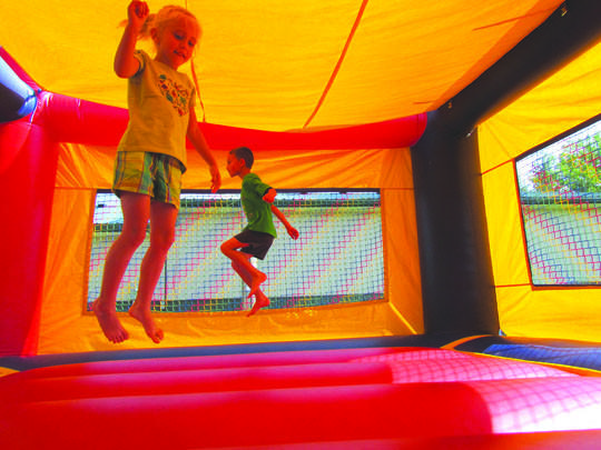 Max Davidson, 7, back, and Emma Schneider, 5, jump around in an inflatable bounce house during the St. John's Celebration in Turton. The St. John's Celebration is a tradition that began more than 100 years ago. American News Photo by Scott Feldman
