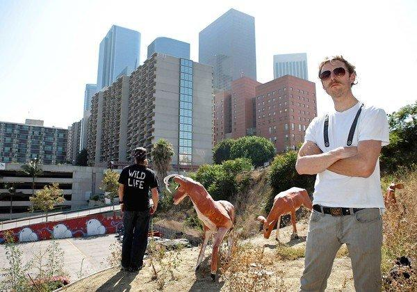 Artist Calder Greenwood, right, and his partner, known only as Wild Life, stand among their most recent installation: three deer perched above a parking lot on Hill Street in downtown Los Angeles.