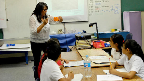 Teacher Mercedes Duron-Flores directs Calexico Unified School District Migrant Program students how to use a hand lens earlier this week. Duron-Flores uses El Centro Elementary School District Science Kits to teach English and science during the summer.