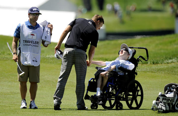 Hunter Mahan shakes the hand of David Finn, 19, after making a birdie putt during the final round of the 2012 Travelers Championship golf tournament at the TPC River Highlands in Cromwell Sunday. Mahan met Finn, who has Leigh's syndrome, a severe neurological disorder, the first year he played and won the Travelers in 2007. Mahan  tied a final round record of -9, 61.