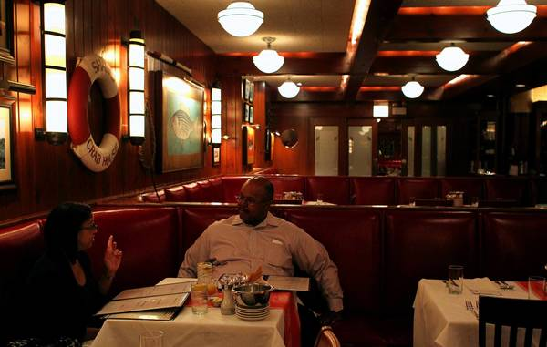 Valerie Alexander, left, and Harrison Greene look over the menu at Shaw's Crab House on Friday. The dining room of the legendary Near North Side restaurant is outfitted in leather booths, white tablecloths and fish art.