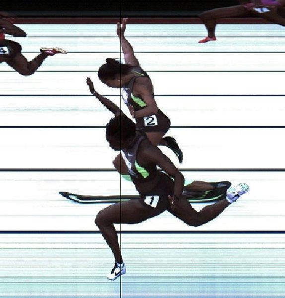 In this handout photo provided by the USTF, Jeneba Tarmoh (bottom, lane 1) and Allyson Felix cross the finish line at exactly the same time in the women's 100 meter dash final during Day Two of the 2012 U.S. Olympic Track & Field Team Trials at Hayward Field.
