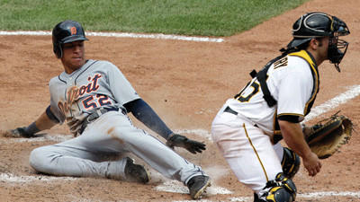 Detroit Tigers' Quintin Berry scores as Pittsburgh Pirates catcher Michael McKenry waits for the late relay throw from right field during the eighth inning on Sunday.