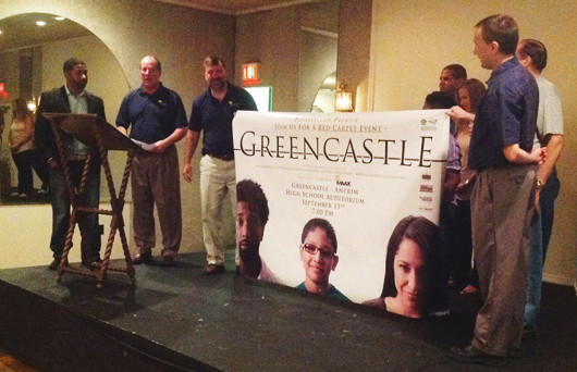 "Koran Dunbar, far left, watches as a banner is revealed for a screening of ""Greencastle."" Proceeds will benefit G-A MAAX, an organization supporting improvements in Greencastle-Antrim, Pa., schools."