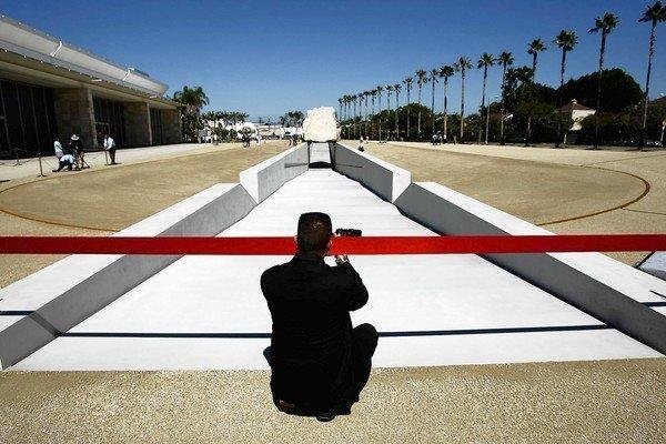 "Photographer Martin Zamora takes a picture of artist Michael Heizer's ""Levitated Mass"" before the ribbon-cutting ceremony at the Los Angeles County Museum of Art on Sunday."