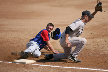 Grotons Mitch Madsen, left, slides into third base as Zach Andera of the Aberdeen Smittys catches the ball on Sunday during the Vern Jark Wood Bat Tournament at Fossum Field. American News Photo by Ryan Deal