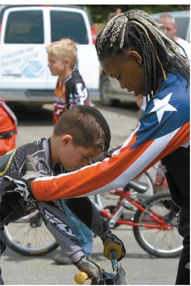 "Professional BMX racer Dominique ""3D"" Daniels coaches second-year rider, Kaden Gaub, 5, of Aberdeen during a BMX clinic on Sunday. American News Photo by Racquel Bethea"