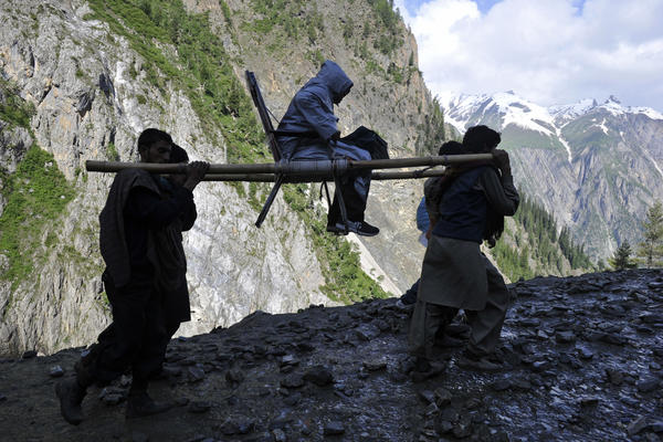 A Hindu devotee is carried by porters during her pilgrimage from Baltal Base Camp to the holy Amarnath Cave Shrine, in Baltal. Every year, hundreds of thousands of pilgrims trek through treacherous mountains to reach the Amarnath cave.