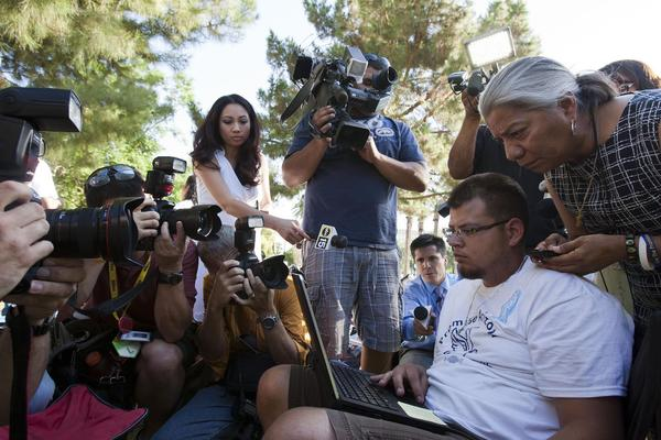 Jose Luis Leal, with laptop computer, and Petra Falcon of Promise Arizona, top right, watch for news about SB 1070 as reporters gather around them at the Arizona Capitol this morning.