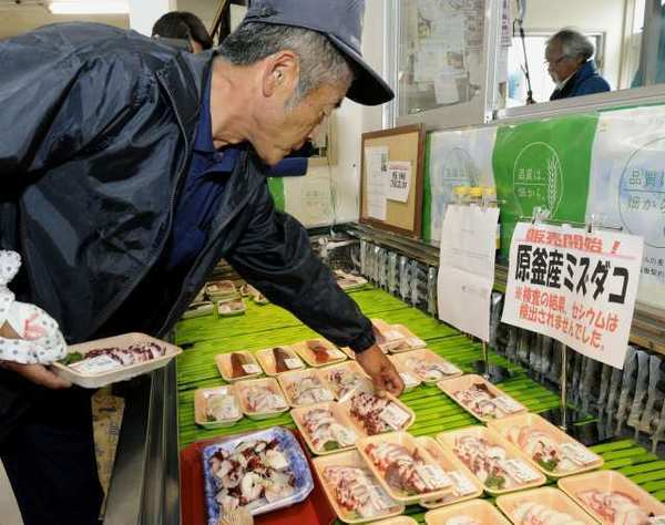 A shopper chooses packs of octopus caught in the waters off Fukushima at a supermarket in Soma, Japan.
