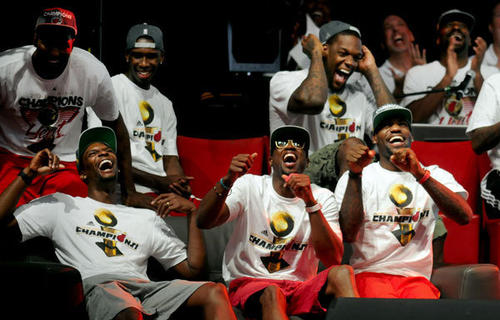 Miami Heat's (front left to right) Chris Bosh, Dwyane Wade,  LeBron James and other teammates laugh as fellow teammate Juwan Howard is interviewed by John Crotty about him being an old timer of the team during the Championship Celebration at the American Airlines Arena in Miami Monday afternoon.