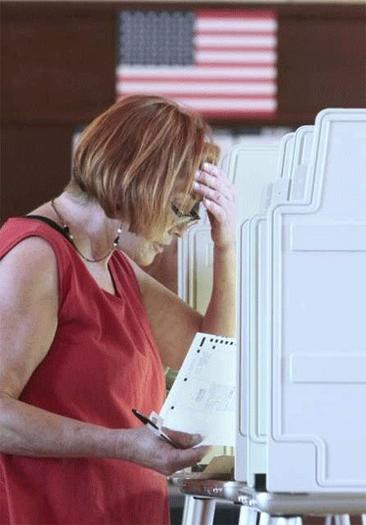 A voter looks over her ballot in Sacramento, Calif.