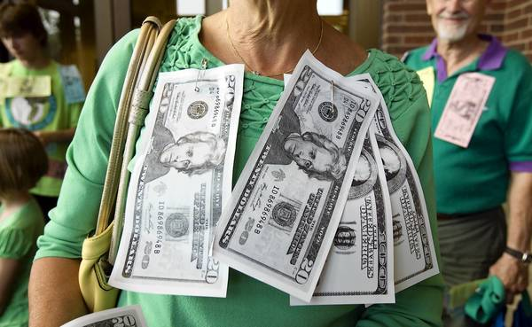 A supporter of Boeger Place covers herself with fake money last week during a rally in the Arlington Heights Village Hall lobby prior to a Village Board meeting.