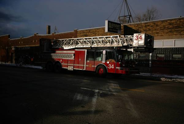 A fire truck is parked at the scene of a fatal fire on the South Side in January 2011. Firefighters, cops and paramedics responding to dangerous vacant buildings would be warned by emergency dispatchers and bright reflective signs under new city efforts to avoid another disaster like the December 2010 roof collapse that killed two firefighters.