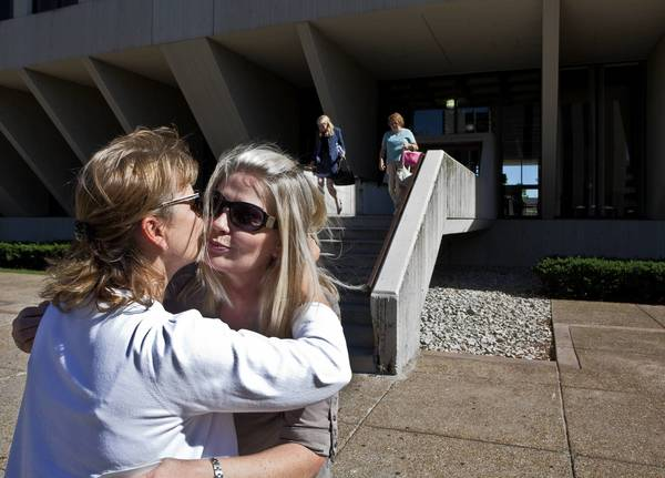 Jan Bartels, right, gets a hug from friend Debbie Minette on Monday as she leaves the Will County Courthouse in Joliet, where Joseph Messina went on trial on charges of aggravated battery against Bartels' son, Eric, who was left blind and paralyzed after being attacked in 2009 outside a Mokena bar.