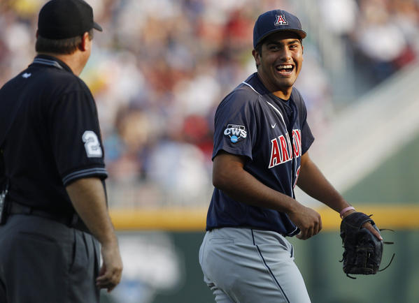 Arizona Wildcats shortsop Alex Mejia (13) laughs while talking to the umpire Gamecocks during the 1st inning.