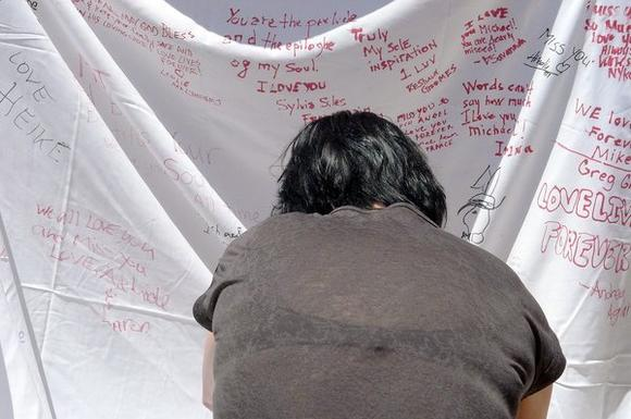 A Michael Jackson fan write on a memorial sheet near his final resting place in Forest Lawn Memorial Park in Glendale, Monday, June 25, 2012.