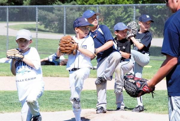Members of the Petoskey Northmen Baseball Skills Camp practice pitching technique at the opening day of the camp Monday at Bates Park.