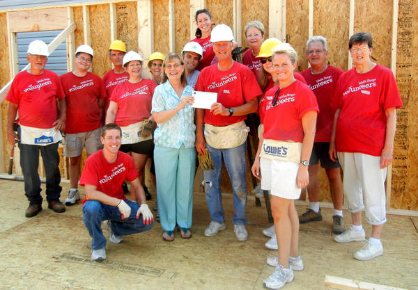 "Jim Sellgren, managing director of Sellgren Financial Group of Wells Fargo Advisors LLC, presents a check for $10,000 to Sherry Brown Cooper, executive director of Washington County's Habitat for Humanity chapter. Also pictured, in no particular order, are Karen Jenneke, Brenda Albert, Dennis Albert; Robert Graves, Ryan Flurie, Kim Blenckstone, Stephanie Kennedy, Wendy Werner, Robert ""Buck"" Shipley, Doris Burdick, Brenna Ranieli, Matt Ranieli, Tom Frame and Ted Compher."