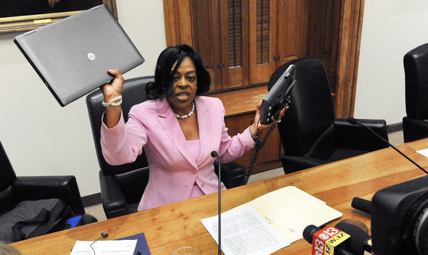 City Comptroller Joan Pratt holds up a computer and a phone as she speaks to reporters about the city's decision to spend $700,000 on a new communications system. Pratt says the purchase was illegal.
