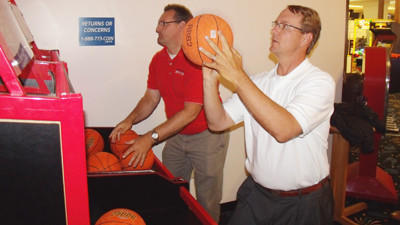 Petoskey Regional Chamber of Commerce president and Stars and Stripes Committee chairman Carlin Smith (left) and Harbor Springs Area Chamber of Commerce executive director Daniel DeWindt compete at a free-throw basketball arcade game Monday at Northern Lights Recreation in Little Traverse Township.