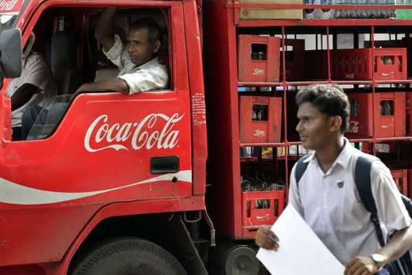 A man walks past a truck that distributes Coca Cola in Mumbai, India. The world's biggest beverage maker said Tuesday that it will invest an additional $3 billion in India through 2020.