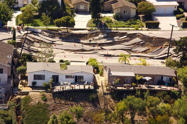 A massive, approximately 200' x 240', sinkhole opens up and tears apart the pavement of Soledad Mountain Road, October 3, 2007 in the Mount Soledad neighborhood of La Jolla near San Diego, California. The landslide has damaged or destroyed reportedly 6 homes and forced the evacuation of at least 20 others.