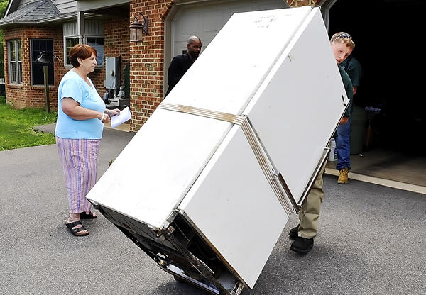 Mary Crumrine watches as her old refrigerator is hauled out of her garage Tuesday under Potomac Edison's Appliance Recycling Program.