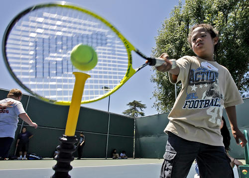 Eight-year old Marc Williams swings at a tennis ball during the annual Jensen-Schmidt Tennis Academy for Special Needs individuals at the Burbank Tennis Center in Burbank on Tuesday, June 26, 2012.