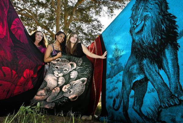 Paula Valenzuela, left, and daughters Elizabeth, middle, and Mariana show off some of the family's collection of San Marcos blankets in El Centro.